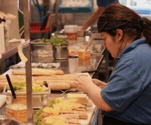 Dame som lager baguetter med ost og salat